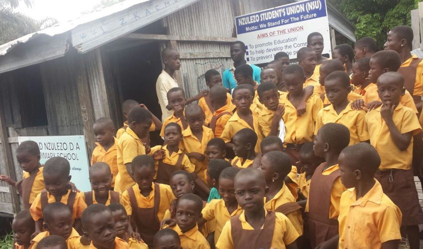 Some students and staff of Nzulezo District Assembly Primary School gathered on the school compound.