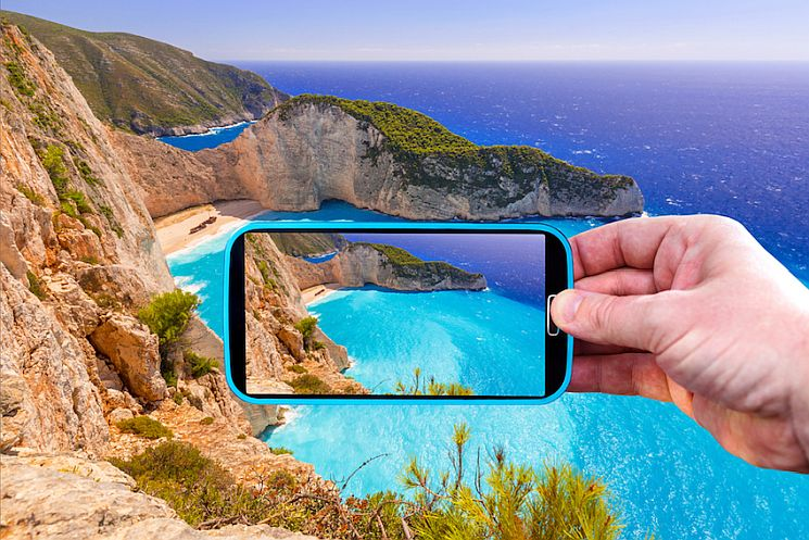 Making photos by smartphone of Navagio beach in Greece.