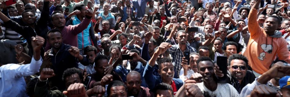 At least 400 young men joined the protest at Jawar's house in the capital Addis Ababa while some two dozen police officers stood nearby [Tiksa Negeri:Reuters]