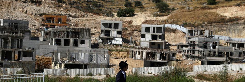 A Jewish settler walks past Israeli settlement construction sites in the Israeli-occupied West Bank near Jerusalem on June 30. (Ammar Awad/Reuters)
