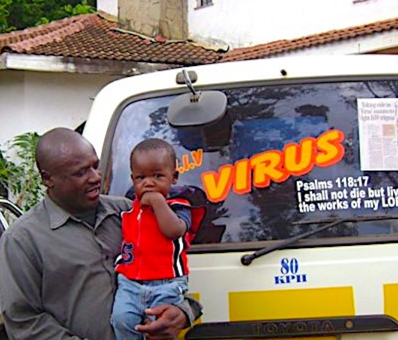 "A FORUM member ""living positively with AIDS,"" pictured with his son. He uses his matatu (taxi) to send messages to the community about positive living and preventing HIV/AIDS"